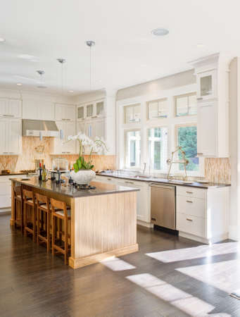 granite kitchen: kitchen interior in new luxury home with island, sink, white cabinets, and hardwood floors