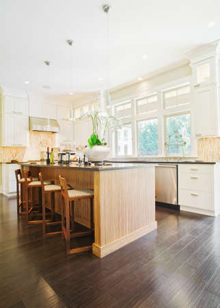 hardwood: kitchen interior in new luxury home with island, sink, white cabinets, and hardwood floors