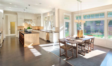 remodel: kitchen interior in new luxury home with island, sink, white cabinets, and hardwood floors