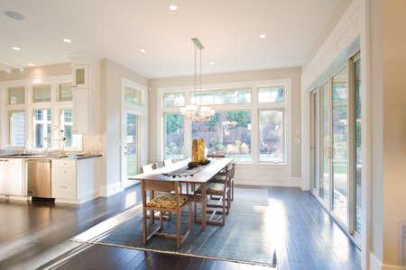 familia cenando: Comedor interior con pisos de madera en Nueva Casa de lujo