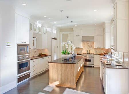 cucina moderna: cucina interni nella nuova casa di lusso con l'isola, lavello, armadi bianchi, e pavimenti in legno