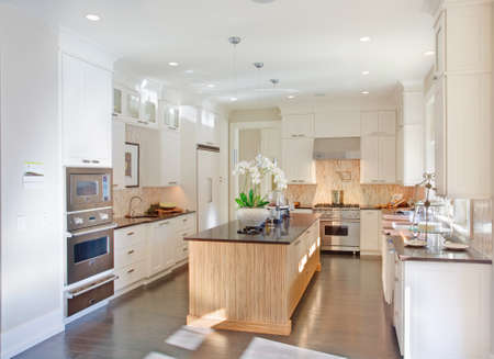 contemporary kitchen: kitchen interior in new luxury home with island, sink, white cabinets, and hardwood floors