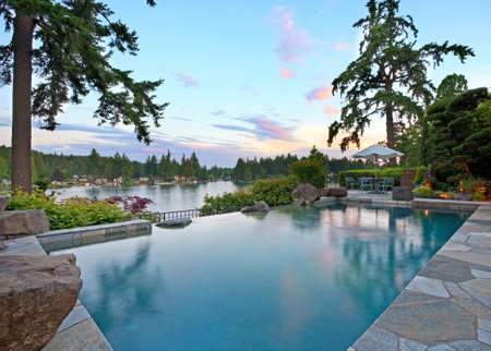 swimming pool home: Home Exterior: Luxurious Outdoor Pool on Lake Stock Photo