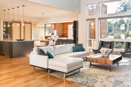Mooie woonkamer onder in een nieuw luxe huis met uitzicht op de keuken. Interhome met hardhouten vloeren en open plattegrond tonen eetkamer, keuken en woonkamer. Heeft hoge gewelfde plafonds. Stockfoto