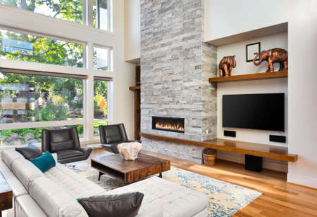 Beautiful living room with hardwood floors and fireplace in new luxury home. Has very tall vaulted ceiling and bank of windows, along with floor to ceiling fireplace and beautiful green plants outside Banque d'images