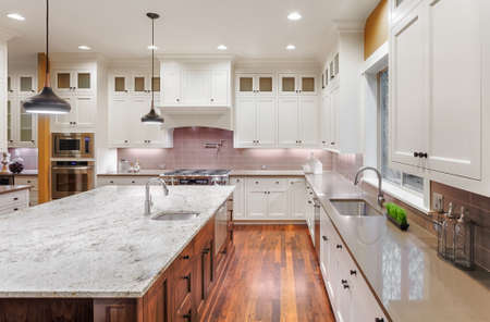 beautiful kitchen interior in new luxury home. kitchen with island, hardwood floors, pendant lights, and cabinets in new luxury home Archivio Fotografico