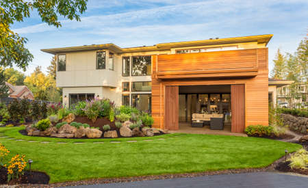 large doors: Beautiful Luxury Home Exterior  with Balcony and Green Grass on Sunny Afternoon