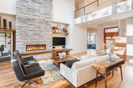 Piękny salon z drewnianą podłogą i kominkiem w nowym luksusowym domu