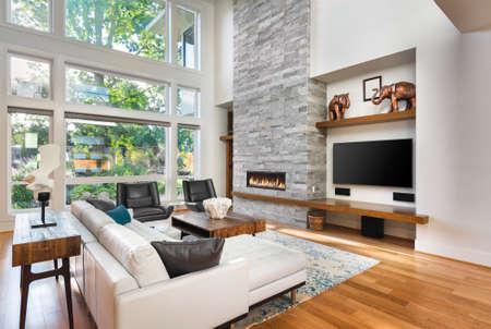 Bel soggiorno con pavimenti in legno e camino nella nuova casa di lusso. Ha molto alto soffitto a volta e banca delle finestre, insieme a pavimento al soffitto camino e belle piante verdi fuori