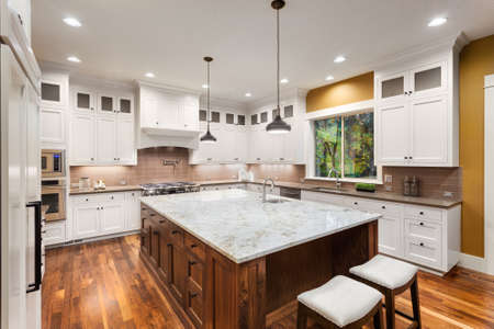 contadores: Interior Grande Cocina con Isla, fregadero, armarios blancos, luces pendientes, y pisos de madera en New Luxury Home Foto de archivo