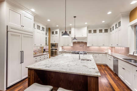 cucina moderna: Grande interni cucina con isola, lavello, armadi bianchi, luci del pendente, e pavimenti in legno in Nuova casa di lusso