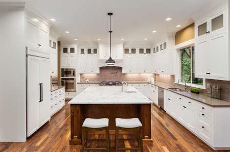 Große Küche Interieur mit Insel, Wasch- oder Spülbecken, weiße Schränke, Pendelleuchten, und Holzfußböden in New Luxury Home