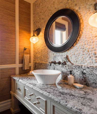 bathroom tiles: bathroom interior in new luxury home. half bath with sink, counter, and mirror. Stock Photo