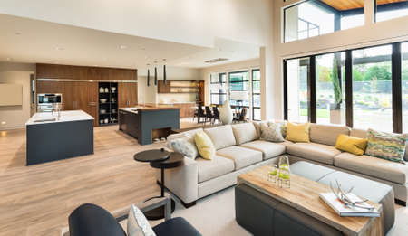 Beautiful living room interior in new luxury home with view of kitchen. Home interior with hardwood floors and open floorplan showing dining room, kitchen, and living room. Has high vaulted ceilings. Foto de archivo