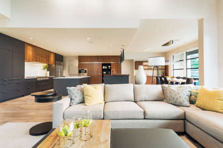 floorplan: Beautiful living room interior in new luxury home with view of kitchen. Home interior with hardwood floors and open floorplan showing dining room, kitchen, and living room. Has high vaulted ceilings. Stock Photo