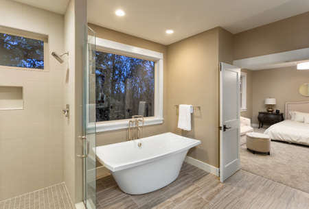 bathroom interior: beautiful master bathroom with bathtub and shower in new luxury home with view of bedroom