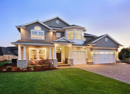 house property: home exterior at nighttwilight with beautiful green grass three-car garage, and driveway Stock Photo