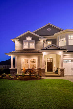 new luxury home at night with beautiful green lawn and covered porch