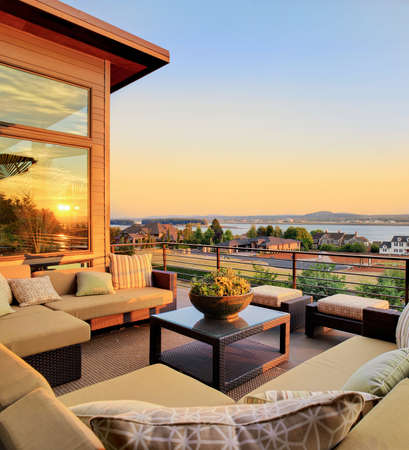 patio outside luxury home with beautiful sunset view of city and river, and colorful sky Foto de archivo