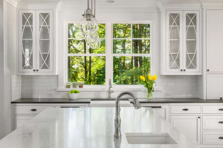 cabinetry: Kitchen in new home with island, two sinks, window view of vibrant green trees, pendant lights, and cabinetry
