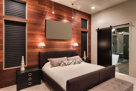 Furnished master bedroom interior in new home with view of bathroom including shower and bathtub Stock Photo