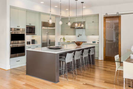 Kitchen Interior with Island, Sink, Cabinets, and Hardwood Floors in New Luxury Home with Lights On