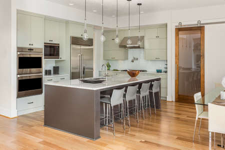 Kitchen Interior with Island, Sink, Cabinets, and Hardwood Floors in New Luxury Home with Lights Off
