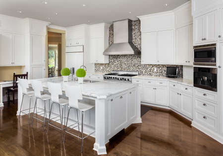 Kitchen Interior with Island, Sink, Cabinets, and Hardwood Floors in New Luxury Home Foto de archivo