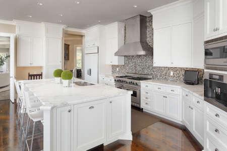 contadores: Interior de la cocina con isla, fregadero, armarios, y pisos de madera en Nueva Casa de lujo