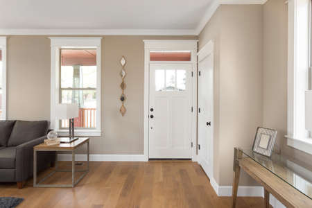 Entryway and Foyer in New Home: Front Door with Hardwood Floors, Window and Couch
