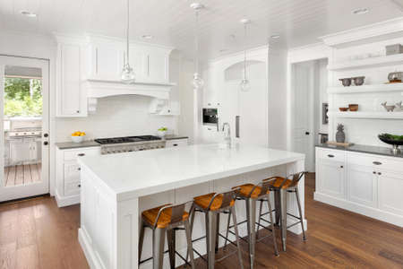 expensive granite: White Kitchen Interior with Island, Sink, Cabinets, and Hardwood Floors in New Luxury Home Stock Photo
