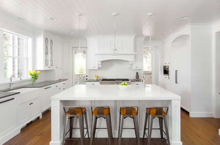 White Kitchen Interior with Island, Sink, Cabinets, and Hardwood Floors in New Luxury Home Stock Photo