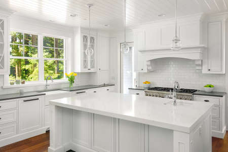 White Kitchen Interior with Island, Sink, Cabinets, and Hardwood Floors in New Luxury Home Standard-Bild