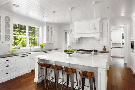 White Kitchen Interior with Island, Sink, Cabinets, and Hardwood Floors in New Luxury Home Stok Fotoğraf