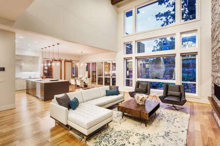 gran salón con techos abovedados en casa de lujo, con gran banco de ventanas, vista de la cocina y mobiliario Foto de archivo