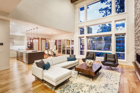 large living room with vaulted ceilings in new luxury home, with large bank of windows, view of kitchen and furnishings
