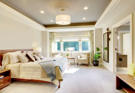 master bedroom in new luxury home with tray ceiling, carpeted floor, large bed, view of bathroom, and sitting area
