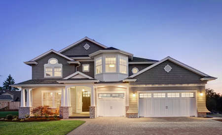 exterior walls: Beautiful luxury home exterior at night, with three car garage, driveway, grass yard, and covered porch