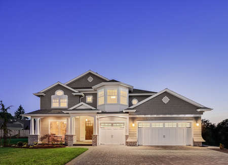 Beautiful luxury home exterior at night, with three car garage, driveway, grass yard, and covered porch. Includes large amount of copyspace