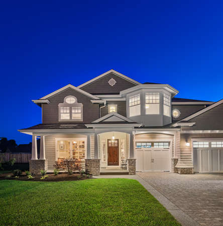 luxury home at night with covered porch, vibrant green grass, and driveway