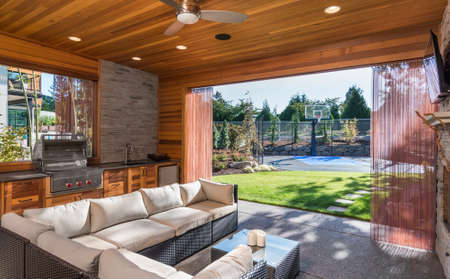 Patio cubierto con barbacoa y hermosa vista del patio ajardinado y cancha de baloncesto como parte del nuevo hogar de lujo