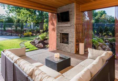 Beautiful Covered Patio with Fireplace, Television, and View of Landscaped Yard as Part of New Luxury Home 스톡 콘텐츠