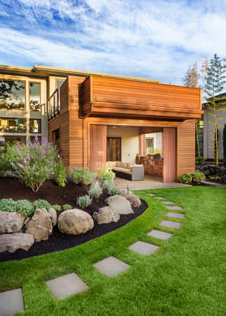 Beautiful home exterior on sunny afternoon, with green grass, walkway, elegant landscaping, covered patio with barbecue, and balcony Archivio Fotografico
