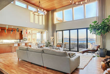 Living room with vaulted ceilings, hardwood floors, and view in new luxury home Banco de Imagens