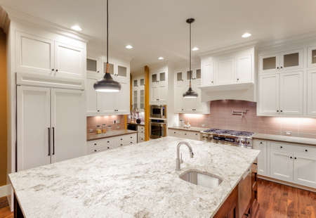 Kitchen Interior with Island, Sink, Cabinets, and Hardwood Floors in New Luxury Home Banco de Imagens