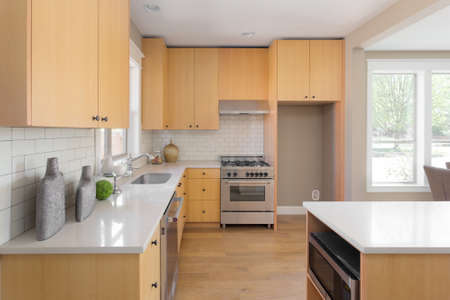 Kitchen Interior with Island, Sink, Cabinets, and Hardwood Floors in New Luxury Home Stock Photo