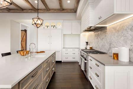Kücheninterieur mit Island, Spüle, Schränke und Holzfußböden in New Luxury Home