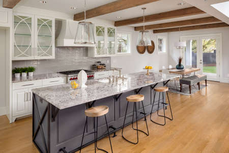 Amazing Kitchen in New Luxury Home with Glass Fronted Cabinets, Island, and Hardwood Floors. Includes View of Dining Room. Lights are off Stock Photo