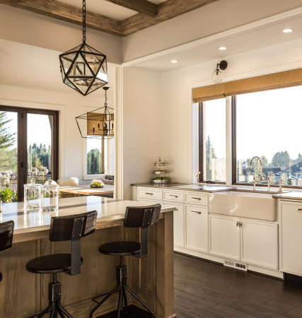 Kitchen Interior Detail with Island, Sink, Cabinets, Elegant Pendant Light, and Hardwood Floors, in New Luxury Home