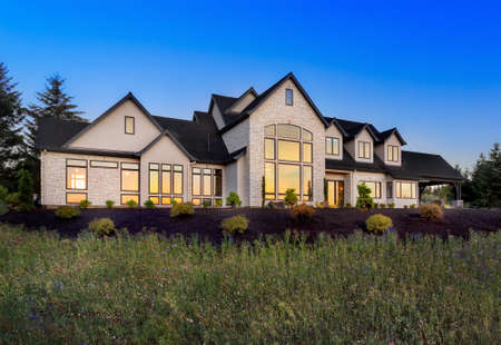 Beautiful Luxury Home Exterior at Night with Sunset Reflection in Windows Banco de Imagens